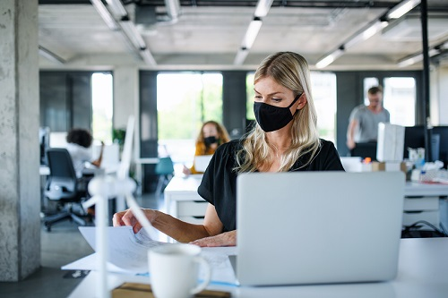 Woman with face mask working in office