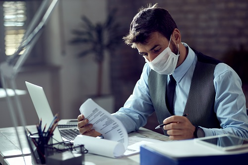 Man in office working with face mask