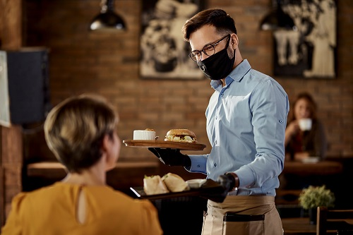 Waiter serving food with mask on
